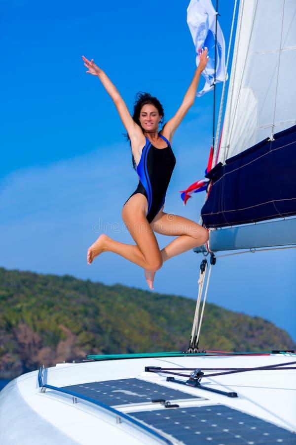 Ung lycklig kvinna i svart baddr?kt som tycker om aftonsolen p? yachten royaltyfria bilder
