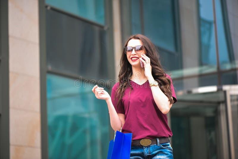 Ung lycklig kvinna med shoppingpåsar som går på gatan royaltyfri bild
