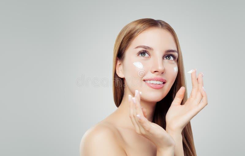 Ung lycklig kvinna med sund hud som applicerar kosmetisk kräm Skincare, skönhet och ansikts- behandlingbegrepp royaltyfria bilder