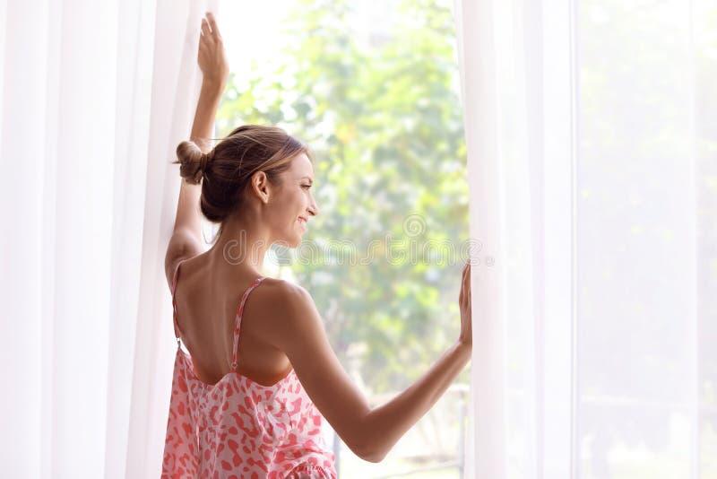 Ung lycklig kvinna nära fönster hemma arkivfoton