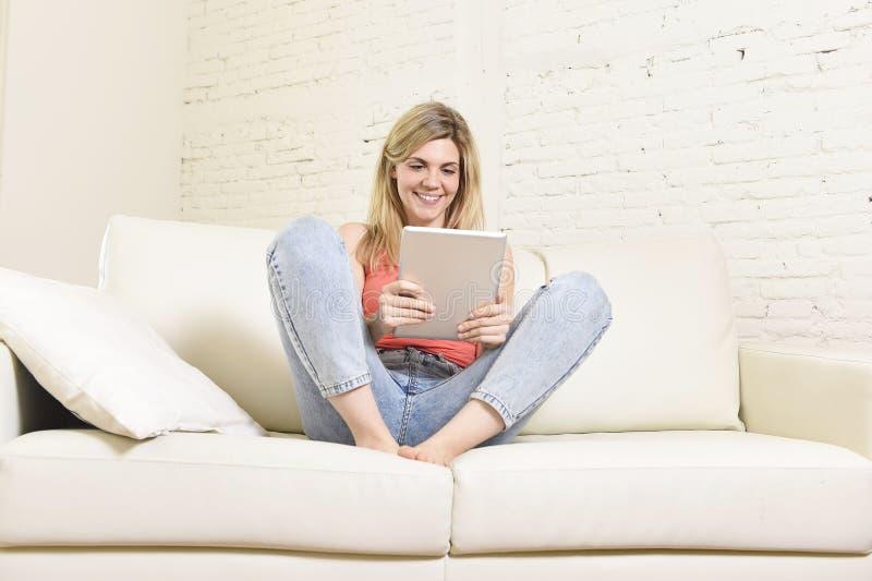 Ung lycklig kvinna på den hem- soffan genom att använda internet app på det digitala minnestavlablocket royaltyfri bild