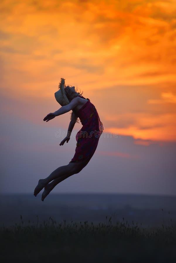 Ung lycklig kvinna på fält i sommarsolnedgång royaltyfri fotografi