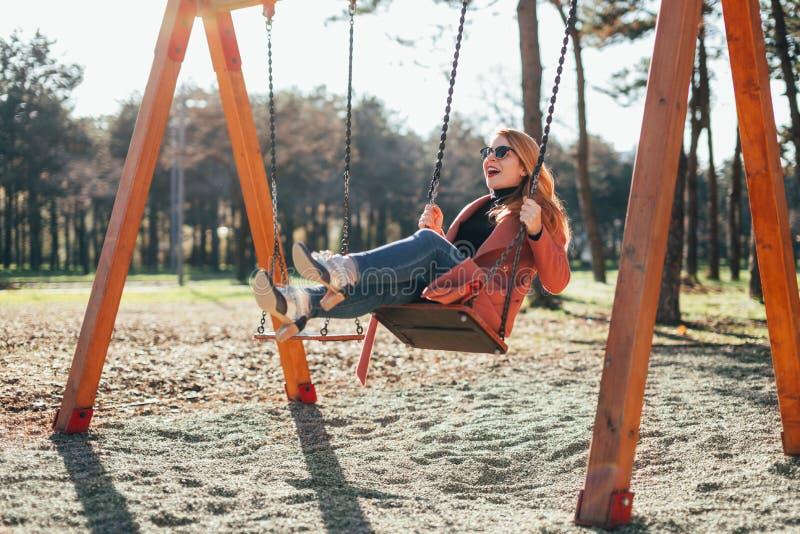 Ung lycklig kvinna på gungan i lekplatsen arkivfoto