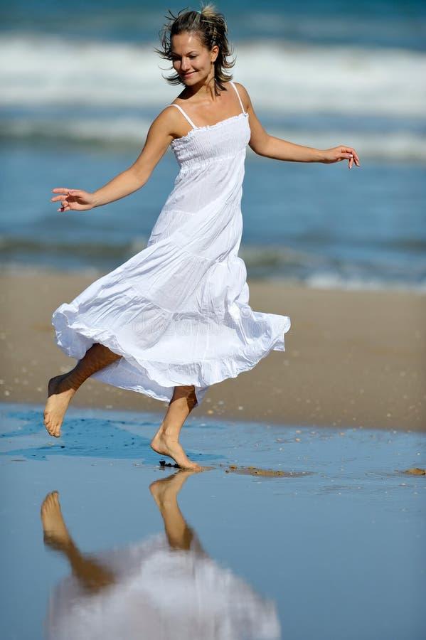 Ung lycklig kvinna på stranden i sommar royaltyfri bild