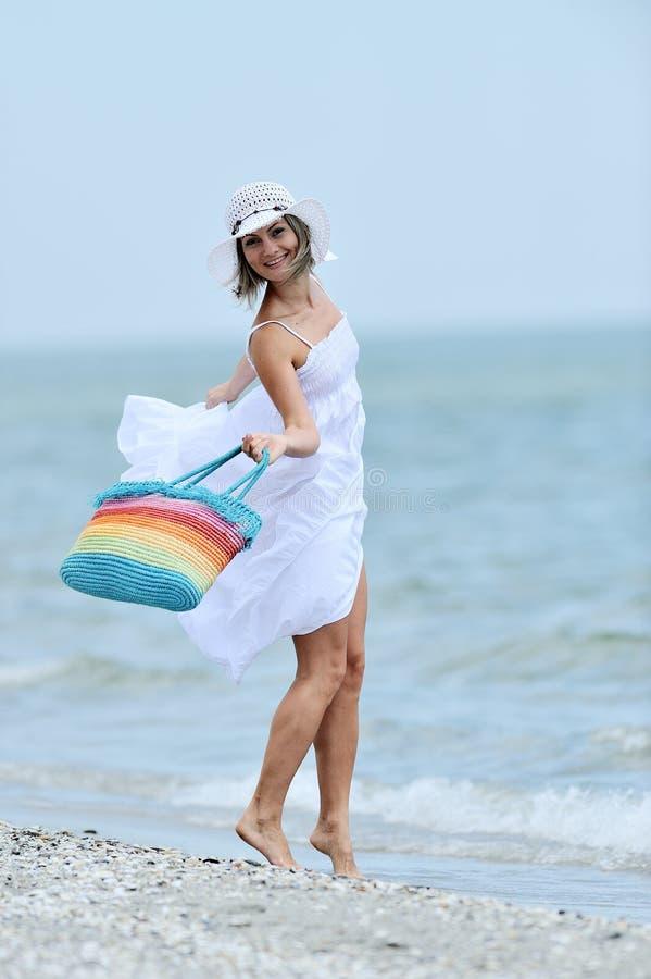 Ung lycklig kvinna på stranden i sommar arkivbilder