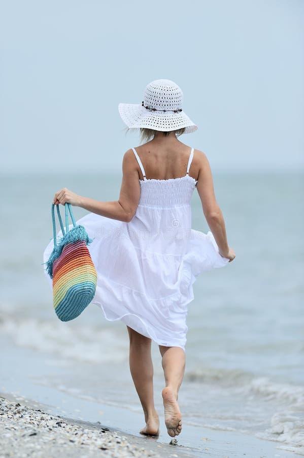 Ung lycklig kvinna på stranden i sommar arkivbild