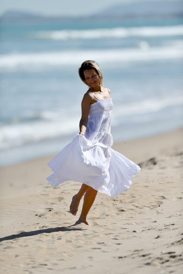 Ung lycklig kvinna på stranden i sommar royaltyfria foton