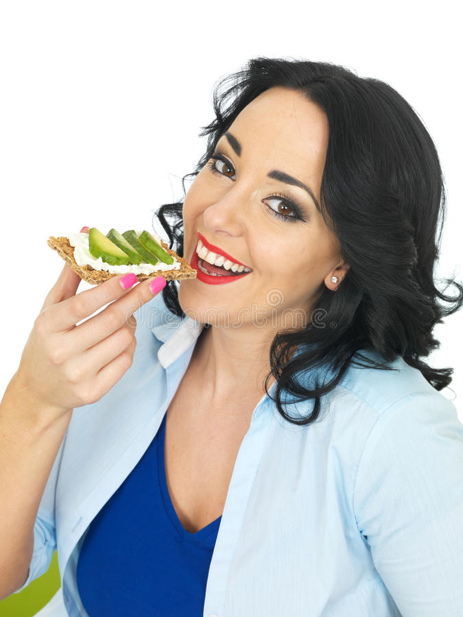 Ung lycklig kvinna som äter en Wholegrain smällare med keso och avokadot arkivfoton