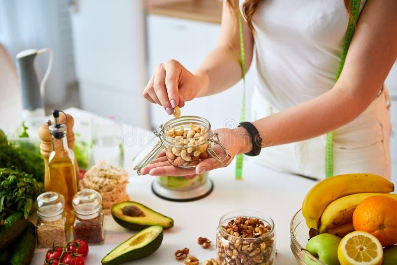 Ung lycklig kvinna som äter olika muttrar kasju, hasselnöt, mandel i modernt kök Sunt mat- och bantabegrepp lossa arkivfoto