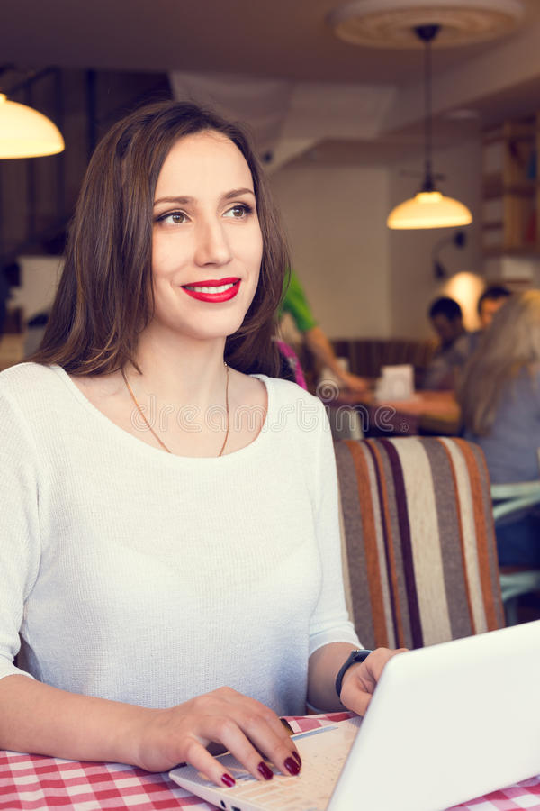 Ung lycklig kvinna som använder anteckningsboken i kafé royaltyfria foton