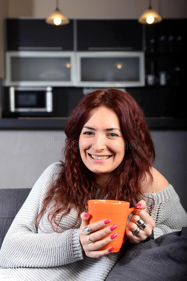 Ung lycklig kvinna som dricker kaffe royaltyfri fotografi