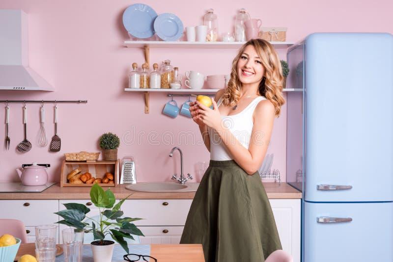 Ung lycklig kvinna som hemma äter frukter i köket Blond härlig flicka som har hennes frukost, innan att gå till royaltyfri bild