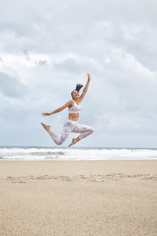 Ung lycklig kvinna som hoppar på stranden fotografering för bildbyråer