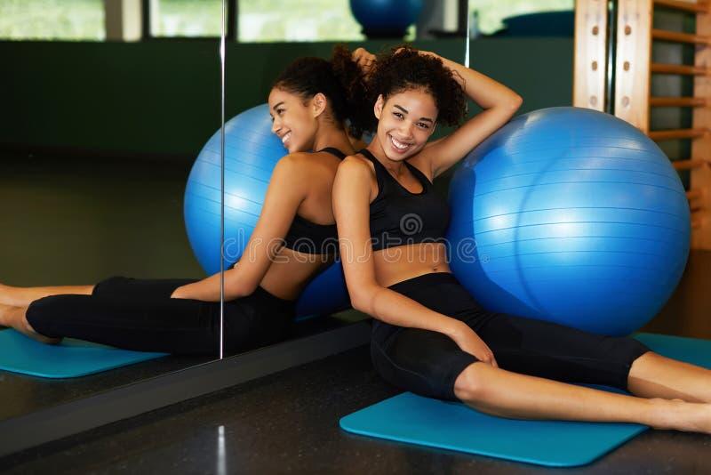 Ung lycklig kvinna som kopplar av efter Pilates gruppsammanträde med passformbollen på det mattt royaltyfri fotografi