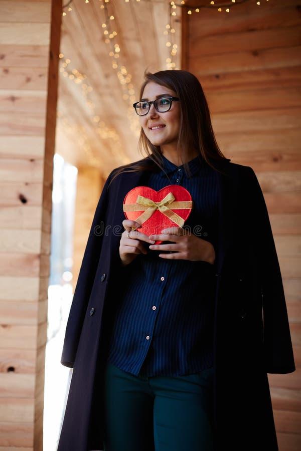 Ung lycklig kvinna som rymmer gåvan och väntar hennes vän arkivfoton
