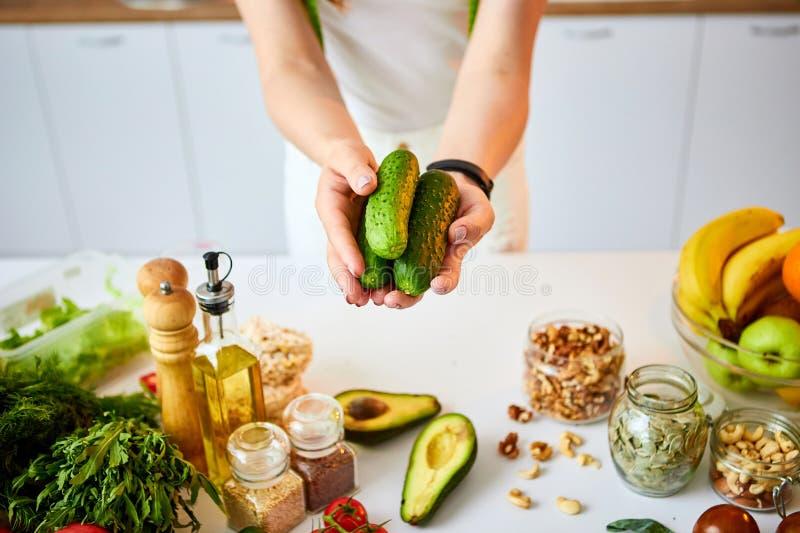 Ung lycklig kvinna som rymmer gurkor för framställning av sallad i det härliga köket med gröna nya ingredienser inomhus sund mat arkivbilder
