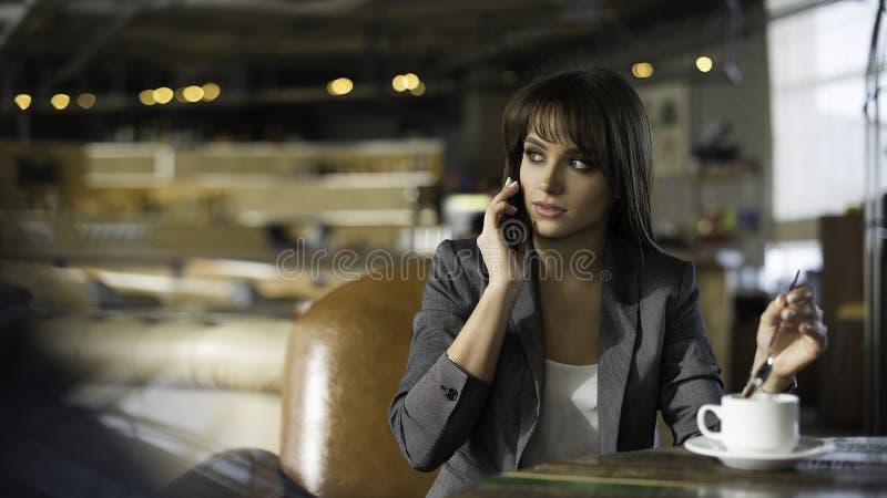 Ung lycklig kvinna som talar på mobiltelefonen med vännen, medan sitta bara i den inre moderna coffee shop och att le hipsterflic royaltyfria foton