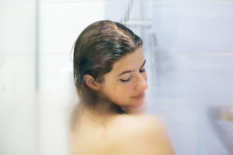 Ung lycklig kvinna som tar den hemmastadda duschen eller hotellbadrummet Den h?rliga brunettflickan som tv?ttar hennes h?r och ty arkivfoto