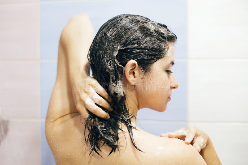 Ung lycklig kvinna som tv?ttar hennes h?r med schampo som skummar med h?nder Den h?rliga brunettflickan som tar duschen och tycke arkivfoton