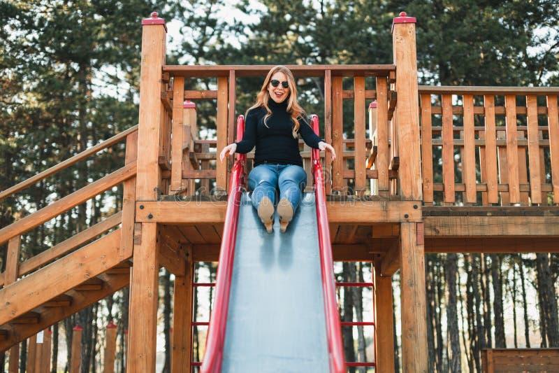 Ung lycklig kvinna som tycker om på glidbanan i lekplatsen royaltyfri foto