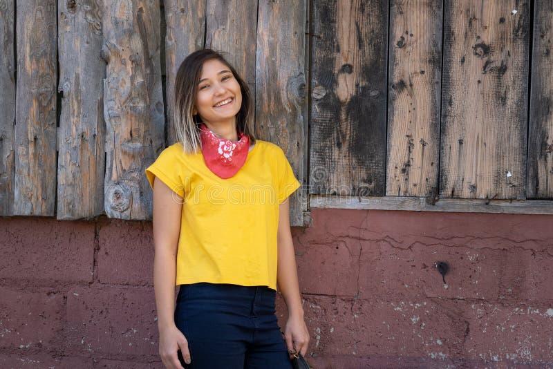 Ung lycklig kvinnastående med den gula t-skjortan arkivfoton