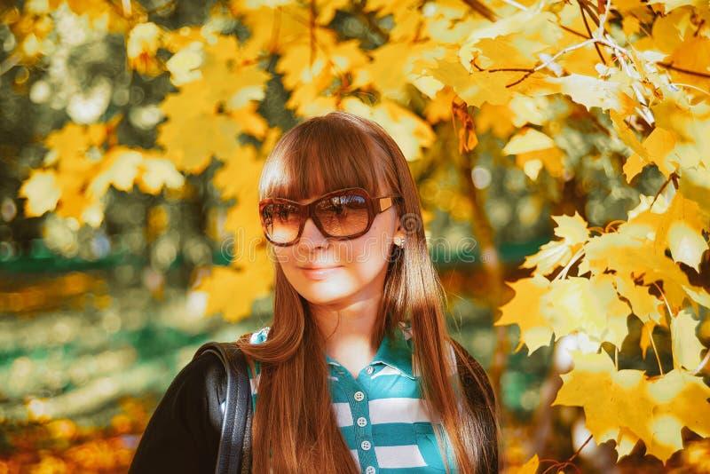 Ung lycklig le flicka i solglasögon nära höstlönnlöv royaltyfri bild