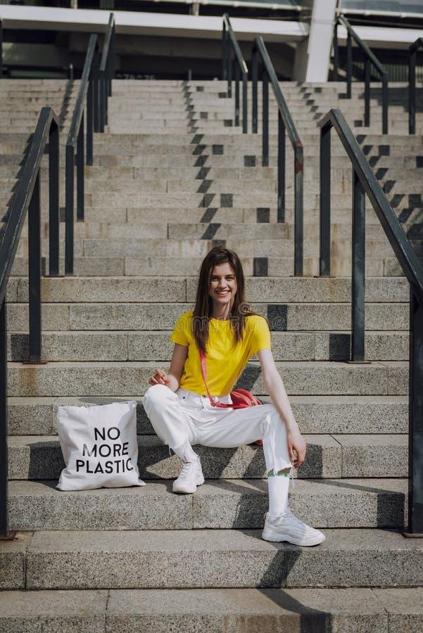 Ung lycklig le flicka som sitter på trappa royaltyfria foton