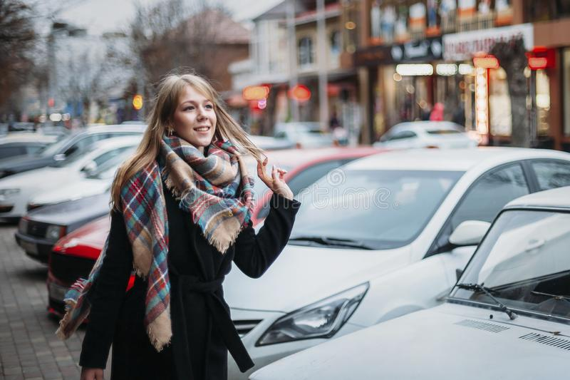 Ung lycklig le kvinna i svart lag och halsduk som går runt om stad Vänta på hennes pojkvän Väntande på möte royaltyfri fotografi