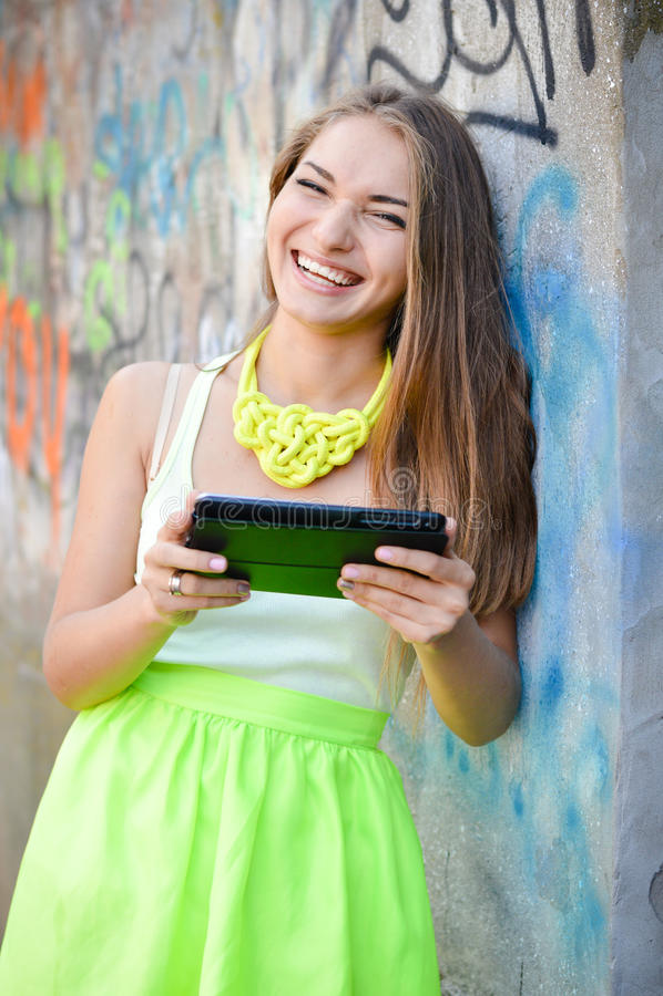 Ung lycklig le kvinna som arbetar på pdaminnestavlaPC royaltyfri bild