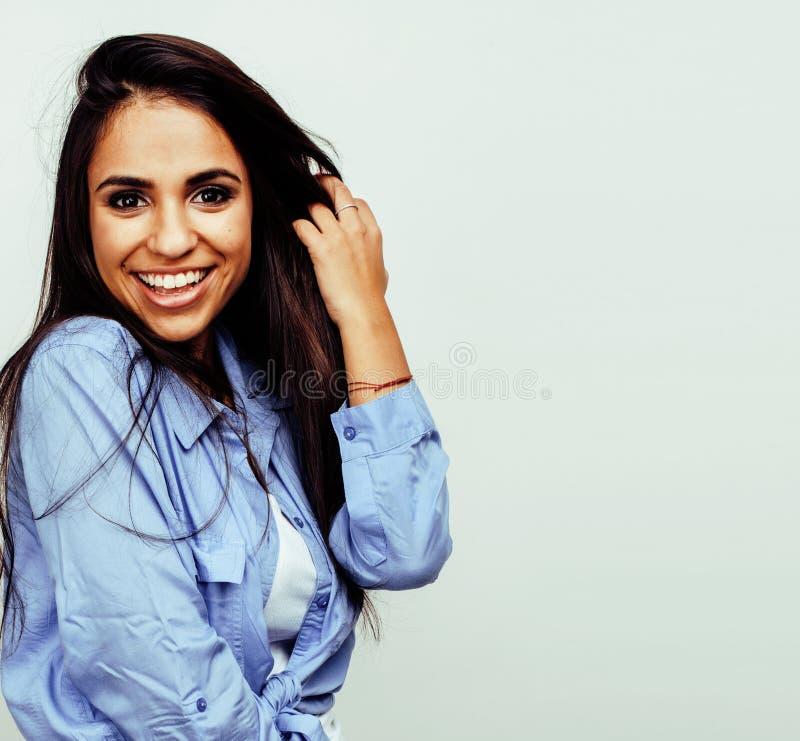 Ung lycklig le latin - amerikanskt emotionellt posera för tonårs- flicka på vit bakgrund, livsstilfolkbegrepp arkivbilder
