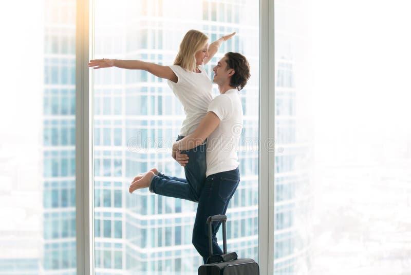Ung lycklig man- och kvinnafamilj i en modern lägenhet royaltyfri foto