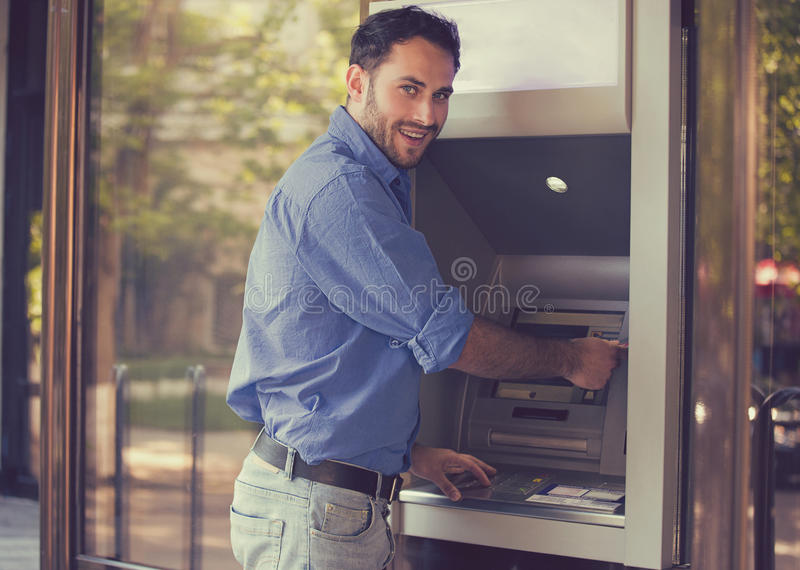 Ung lycklig man som använder ATM royaltyfri bild