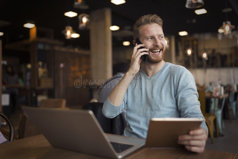 Ung lycklig man som har påringning i kafé arkivbild
