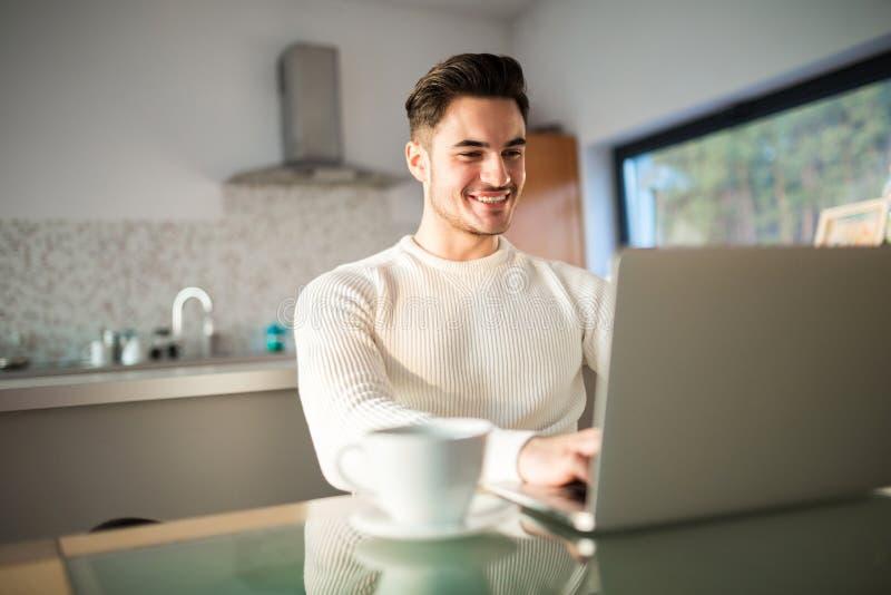 Ung lycklig man som hemma arbetar på bärbara datorn arkivbild