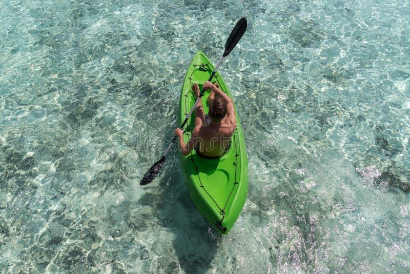 Ung lycklig man som kayaking p? en tropisk ? i Maldiverna bl?tt klart vatten royaltyfria bilder