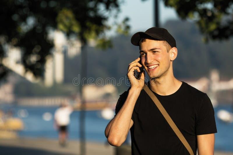Ung lycklig man som talar på telefonen i gatan arkivfoto