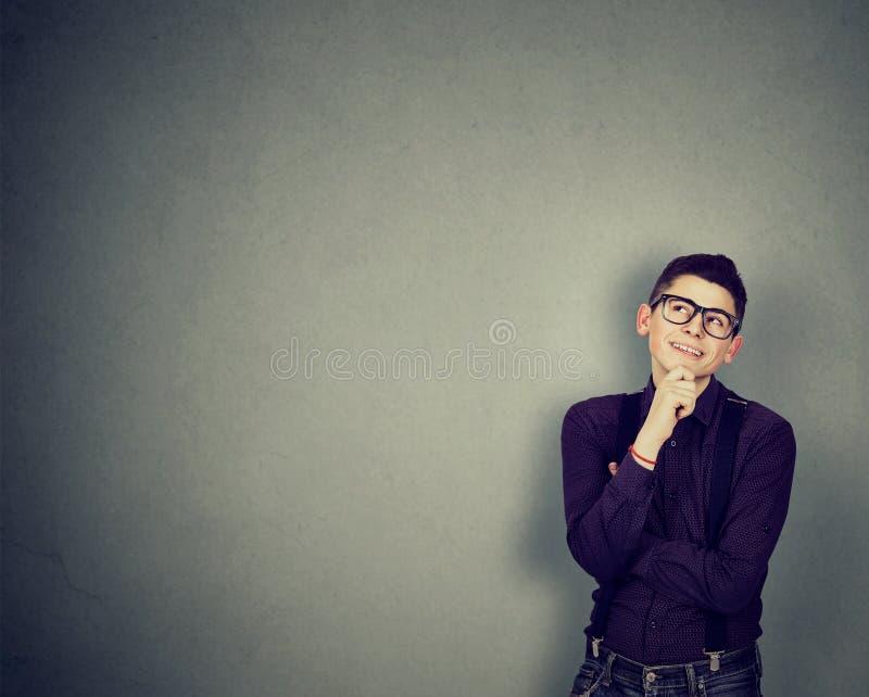 Ung lycklig manbenägenhet på en vägg som ser tänka upp arkivbilder