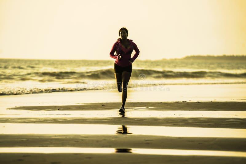 Ung lycklig och attraktiv afrikansk amerikanlöparekvinna som övar på rinnande genomkörare på den härliga stranden som joggar och  royaltyfri fotografi