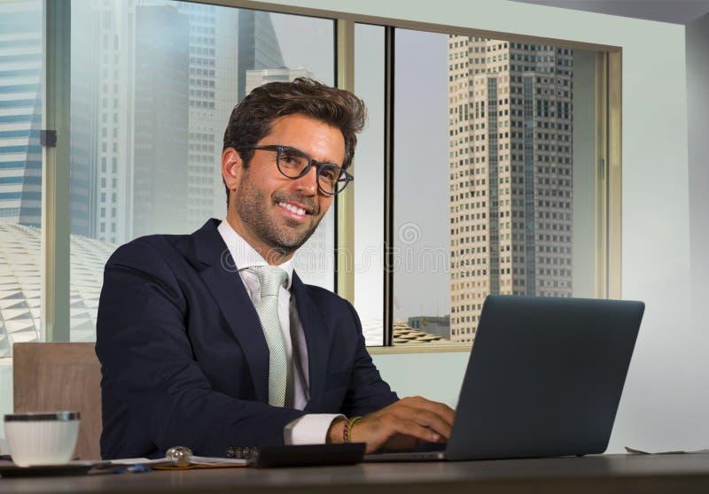 Ung lycklig och attraktiv lyckad affärsman som arbetar på det moderna kontoret i tillfredsställt att le för område för central af arkivbild