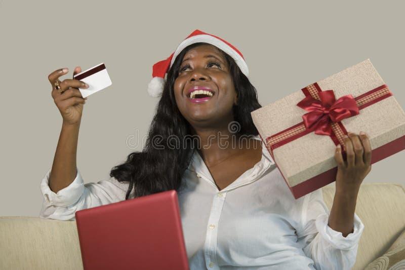 Ung lycklig och attraktiv svart afrikansk amerikankvinna i kreditkort för Santa Klaus hattinnehav och julklappask som gör onl fotografering för bildbyråer