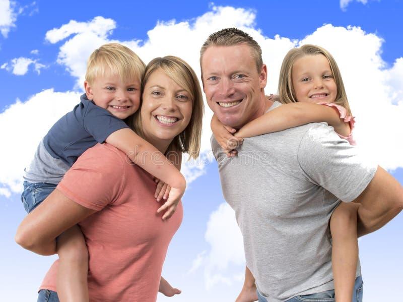 Ung lycklig och härlig amerikansk familj med maken och frun som på bär deras tillbaka lilla son och älskvärda unga dotter i lov arkivfoto