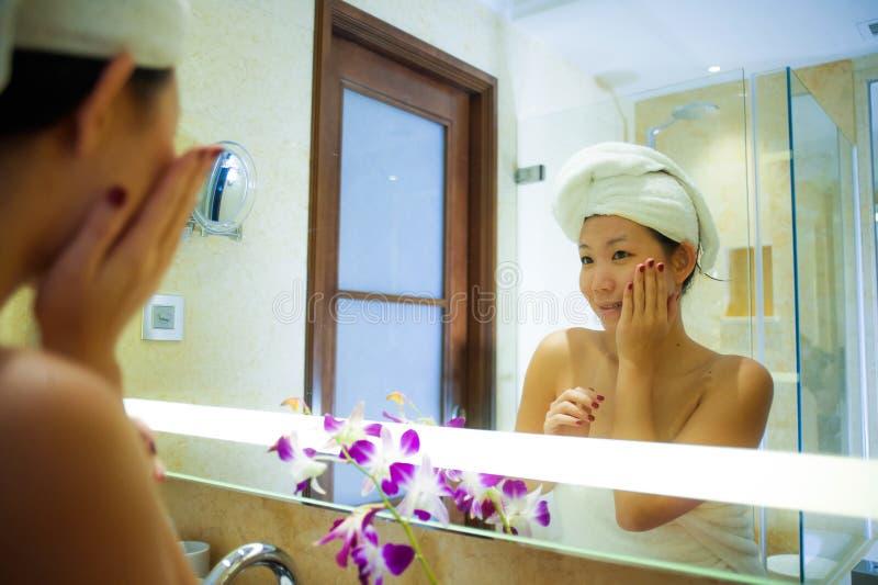 Ung lycklig och härlig asiatisk koreansk kvinna hemma eller hotellbadrum som slås in i toaletthandduken som applicerar gladlynt m royaltyfri bild