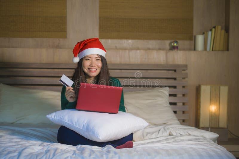 Ung lycklig och härlig asiatisk koreansk kvinna på säng i den Santa Christmas hatten genom att använda kreditkort- och bärbar dat fotografering för bildbyråer
