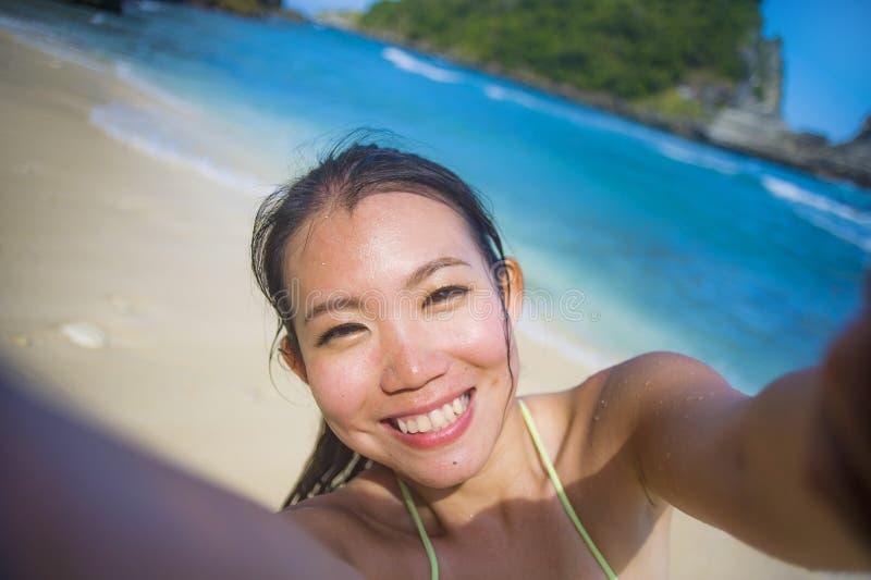 ung lycklig och härlig asiatisk turist- kvinna för korean eller för kines i bikinin som tar självståendeselfiefotoet på paradisst royaltyfri fotografi