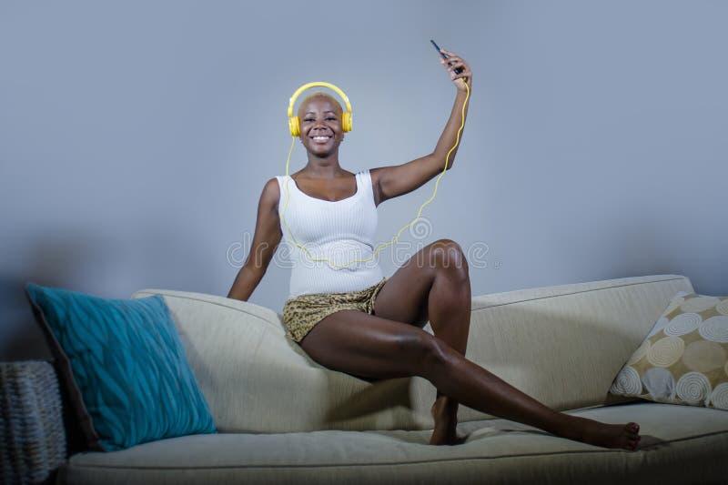 Ung lycklig och härlig avkopplad svart afro amerikansk kvinna som lyssnar till musik med hörlurar och mobiltelefonen som tycker o royaltyfri foto