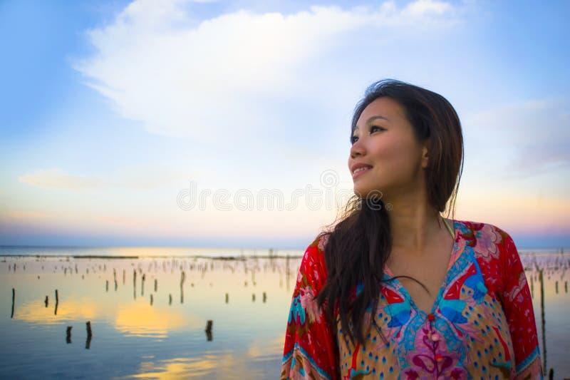 Ung lycklig och härlig koreansk kvinna i traditionell asiatisk klänning på soluppgånghavslandskapet som in ser bort fundersamt oc royaltyfria foton