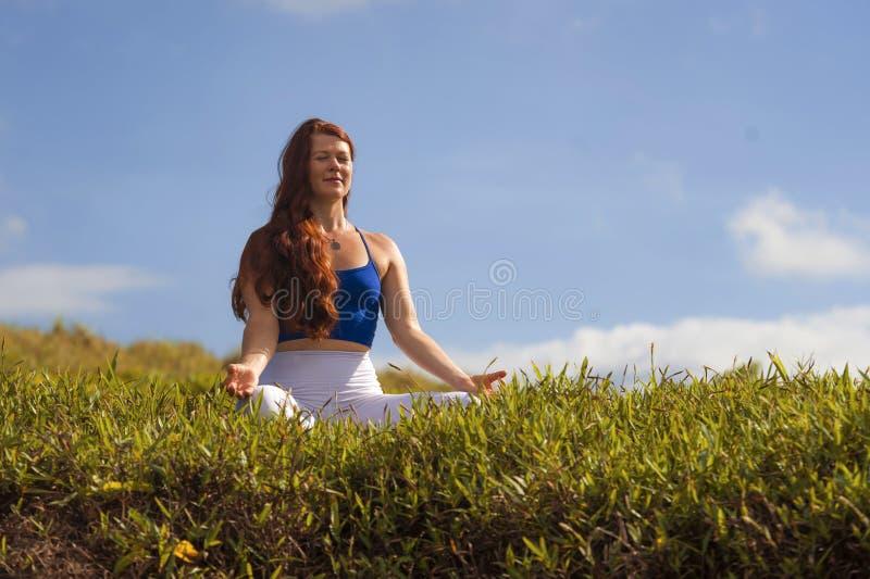 Ung lycklig och härlig röd hårkvinna som sitter på det gröna fältet som kopplas av på den övande yogaövningen för gräs som utomhu royaltyfria bilder
