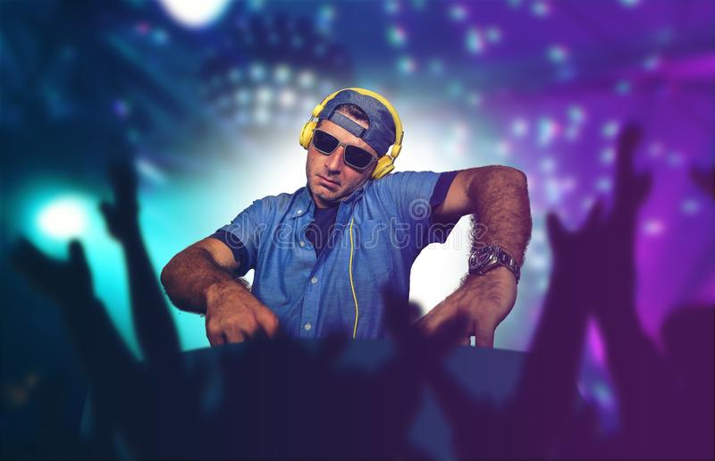 Ung lycklig och kall deejay som spelar musik på partihändelsen i blandande technosånger för nattklubb på laser och prålig l arkivfoto