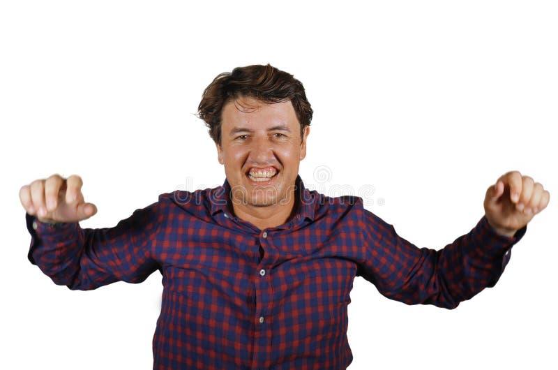 Ung lycklig och upphetsad man som ler gladlynt fira g?ra en gest f?r prestation- eller aff?rsprojektframg?ng som ?r glat och som  arkivfoto