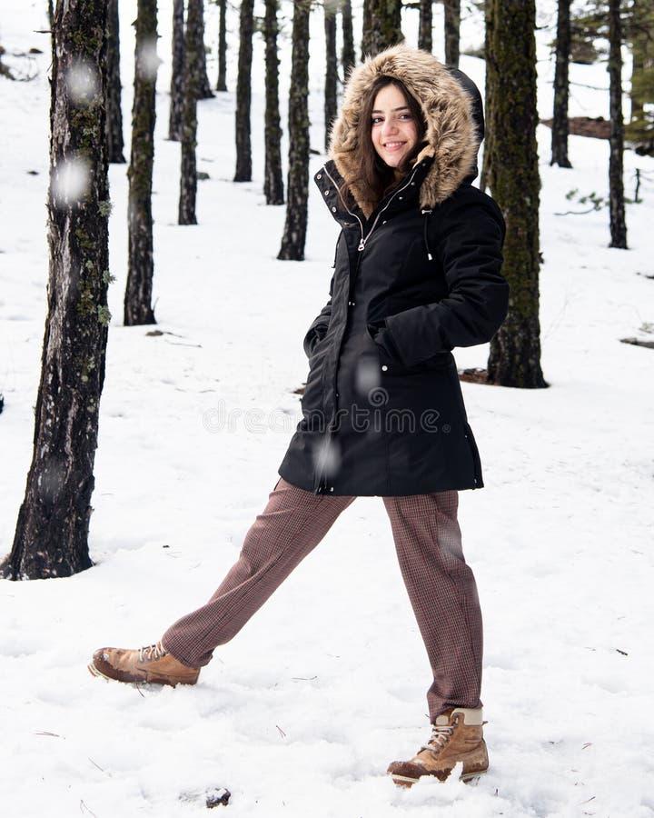 Ung, lycklig och vacker tonårsflicka klädd i vinterkläder som står på snö och leker arkivbild